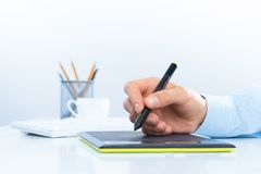 Designer hand drawing a graph on the tablet Royalty Free Stock Photo