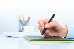 Designer hand drawing a graph on the tablet Stock Photo