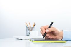 Designer hand drawing a graph on the tablet. Which lies on a white table Royalty Free Stock Image