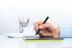 Designer hand drawing a graph on the tablet Royalty Free Stock Photography