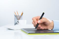 Designer hand drawing a graph on the tablet Royalty Free Stock Image