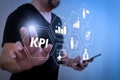 Designer hand pressing an imaginary button,holding smart phone,d. Key Performance Indicator (KPI) workinng with Business Intelligence (BI) metrics to measure Stock Images