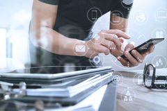 Designer hand using mobile payments online shopping,omni channel. In modern office wooden desk,icons graphic interface screen,eyeglass,filter stock photography