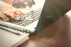 Designer hand working with digital tablet and laptop and notebook stack and eye glass on wooden desk in office. Concept of target focus digital diagram,graph royalty free stock photography