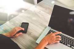Designer hand working and smart phone and blank screen laptop an Royalty Free Stock Photography