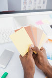 Designer holding colour swatch and choosing Royalty Free Stock Image