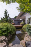 Designer Home with Stream. A water feature emulating a creek flows under a deck and between landscaped rocks with a contemporary home in the background Stock Image