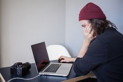 Designer for a laptop, a workplace for freelancers. A young man sitting at a table. With a laptop and a professional camera royalty free stock photos