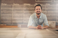 Designer leaning on his workbench smiling positively Stock Image