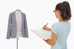 Designer looking at her mannequin and taking notes Stock Photography