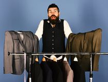 Designer makes choice near clothes hangers. Man with beard. In vest by clothes rack. Fashion choice concept. Tailor with troubled face holds grey suits near stock image