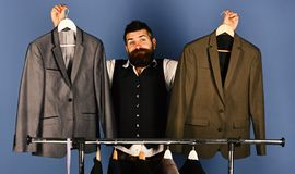 Designer makes choice near clothes hangers. Tailor with confused face holds grey suits near custom jackets on blue. Background. Fashion and individual style royalty free stock image