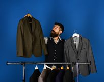 Designer makes choice near clothes hangers. Tailoring and design. Concept. Tailor with curious face holds grey suits near custom jackets on blue background. Man royalty free stock photo