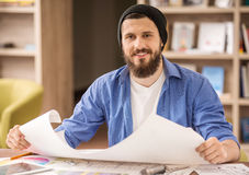 Designer. Male designer dressed casual sitting at the table and holding whatman paper at home office Royalty Free Stock Photos