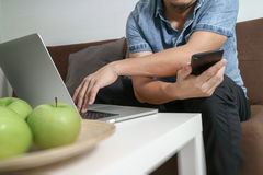 Designer man hand using laptop compter and mobile payments onlin Royalty Free Stock Photo