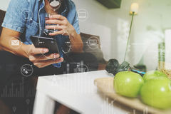 Designer man hand using mobile payments online shopping,omni cha. Nnel,drinking water,sitting on sofa in living room,green apples in wooden tray,graphic interfce Stock Photography