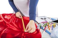 Designer measuring red fabric Royalty Free Stock Image