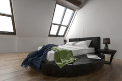 Designer modern bedroom with slanted windows Royalty Free Stock Photography