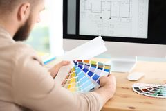 Designer with paint color palette samples at table. Closeup royalty free stock images