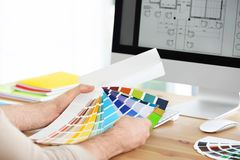 Designer with paint color palette samples at table. Closeup stock photos