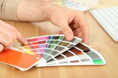 Designer with paint color palette samples at table. Closeup stock photo