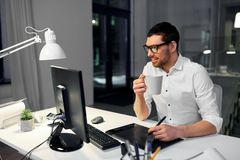 Designer with pen tablet drinking coffee at office. Business, graphic design and technology concept - smiling businessman or designer with computer and pen stock image