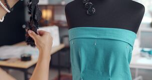 Designer picking up decorative elements for blue dress