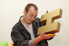 Designer produces three-dimensional letter. Royalty Free Stock Photography