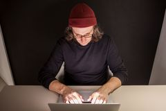 Designer or programmer in the workplace. young man in a hat and glasses sitting at a laptop. stock photos