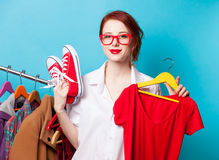 Designer with red dress and gumshoes. Young redhead designer with red dress and gumshoes on blue background Royalty Free Stock Photos