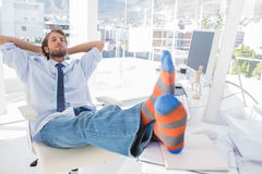 Designer relaxing at desk with no shoes Stock Photo