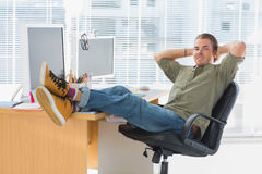 Designer relaxing with foot on the desk Stock Photos