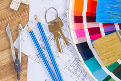 Designer's working table. Interior designer's working table with architectural plan of the house, keys, color palette and brushes royalty free stock photos