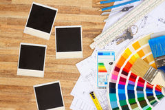 Designer's working table. Interior designer's working desktop with architectural plan of the house, color guide and brushes, copy space on empty instant photos stock images