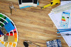 Designer's working table. Interior designer's working desktop with architectural plan of the house, color guide and brushes, copy space on wooden table royalty free stock images