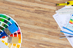 Designer's working table. Interior designer's working desktop with architectural plan of the house, color palette and brushes, copy space on wooden table stock photos