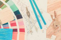 Designer`s working table. Interior designer`s working desktop with architectural plan of the house, keys, color palette and brushes retro toned stock images