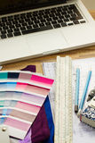 Designer's working table. Interior designer's working desktop with architectural plan of the house, keys, color palette guide and laptop royalty free stock images