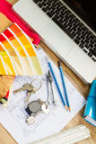 Designer's working table. Interior designer's working desktop with architectural plan of the house, keys, color palette and laptop royalty free stock photos
