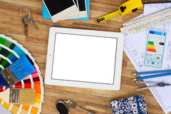 Designer's working table. Interior designer's working desktop flat lay scene with architectural plan of the house, color guide and brushes, copy space on tablet stock photo