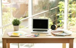 Designer`s workplace with laptop and paint color palette samples. On table stock photography