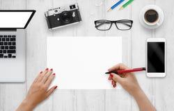 Designer schreibt auf ein leeres Papier Draufsicht des Arbeitsschreibtisches mit Computer, Telefon, Kamera lizenzfreie stockfotos