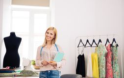 Designer standing in workshop with notebook and pencil Stock Image