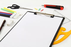 Designer and Stationery Materials. Various designer and stationery materials like ruler, scissors, pens, brushes and a4 blank paper on white desk Royalty Free Stock Images