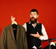 Designer and suit on clothes hanger. Man with beard. In vest by clothes rack. Tailor with surprised face presents grey green suit near custom jackets on red royalty free stock photos