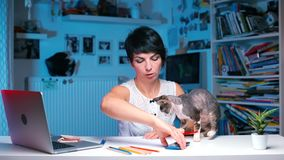 The designer at the table with a cat draws. The designer is sitting at the office desk. There is a cat walking on the table. The girl draws with a pencil, holds stock video