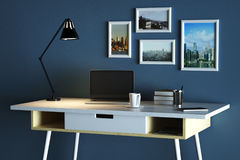 Designer table with empty laptop. Close up of creative designer table with blank laptop, coffee cup, lamp, picture frames and other items on concrete wall Stock Images
