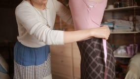 Designer takes measurements measuring tape dress before tailoring for girls stock footage