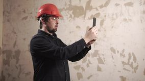 Designer is taking photo of flat under construction by smartphone stock footage