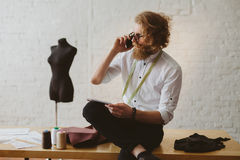 Designer talking phone in parlour stock photography